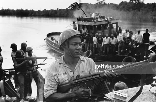 Ibo soldiers using tugboats as transportation down river during the Biafran war
