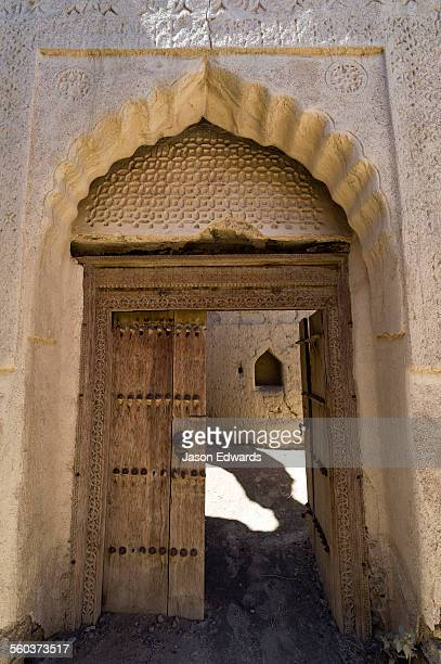 Ornate scalloped stone and mudbrick archways above carved timber lintels and doorways in an abandoned village in the desert.