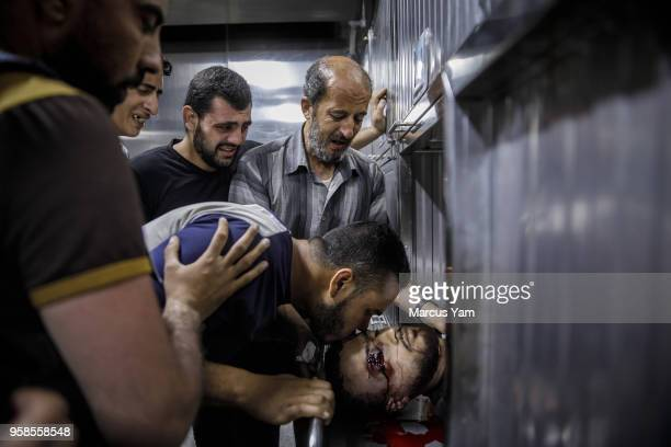 Ibraheem Mohammed AlTubassi father top and othe family members bid farewell to Yazan Ibraheem Mohammed AlTubassi at the Shifa Hospital morgue after...