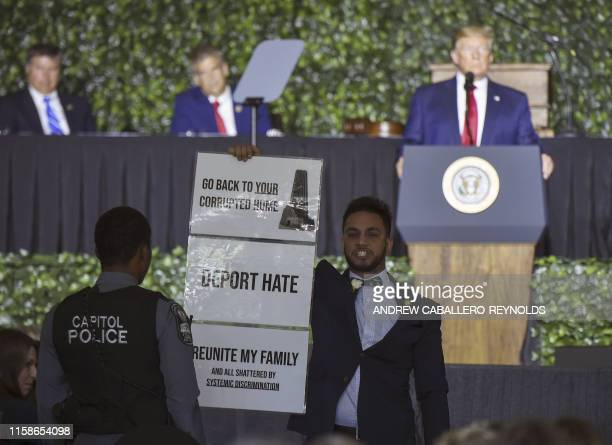 Ibraheem Samirah, a Democratic Virginia assemblyman holds a protest sign as US President Donald Trump speaks during an event commemorating the 400th...