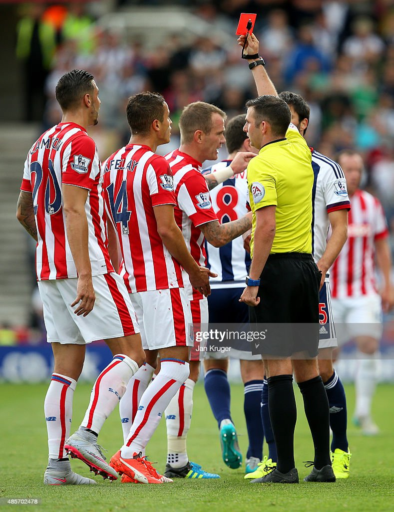 Ibrahim Afellay (2nd L) of Stoke City is shown a red card by referee Michael Oliver (R) during the Barclays Premier League match between Stoke City and West Bromwich Albion at Britannia Stadium on August 29, 2015 in Stoke on Trent, England.