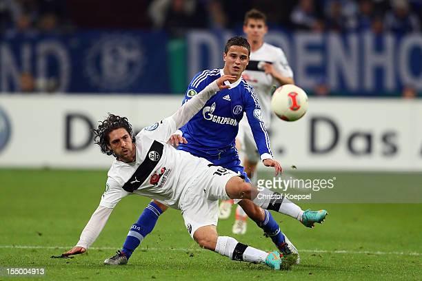 Ibrahim Affelay of Schalke challenges David Ulm of Sandhausen during the DFB Cup second round match between FC Schalke 04 and SV Sandhausen at...