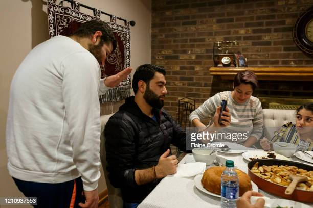 Ibrahim Al Haj Ahmad, left, and Abbas Al Haj Ahmed talk with their cousin Mohamad Al Haj Ahmad over a video call while their family shares a meal and...