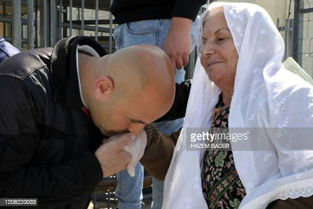 Ibrahim Sweity, a Palestinian released from an Israeli prison, kisses his mother's hand after crossing the Mitar checkpoint in the occupied West Bank...