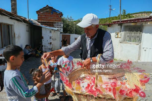 Ibrahim Tenekeci, who produce traditional lollipop for 43 years, walks an average of 10 kilometers a day to sell his products at Bergama district of...