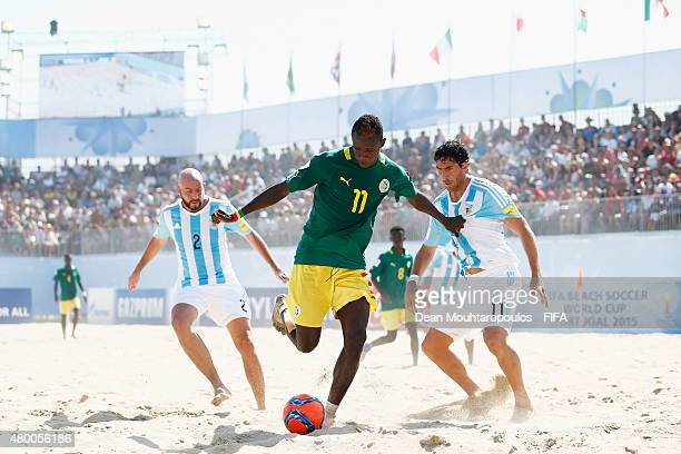 Ibrahima Balde of Senegal battles for the ball with Santiago Hilaire and Miguel De Ezeyza of Argentina during the Group A FIFA Beach Soccer World Cup...