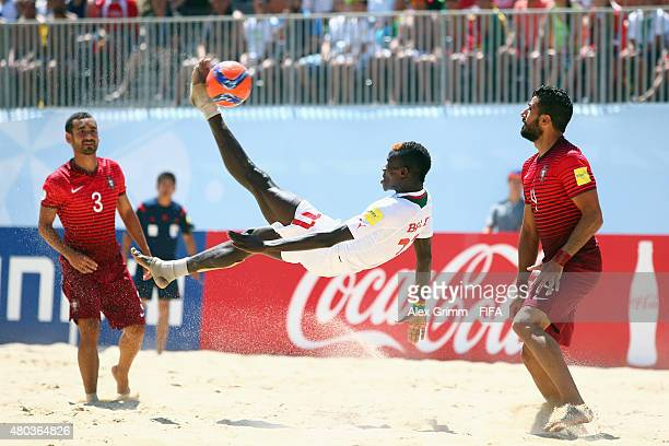 Ibrahima Balde of Senegal does a bicycle kick next to Torres and Leo of Portugal during the FIFA Beach Soccer World Cup Portugal 2015 Group A match...
