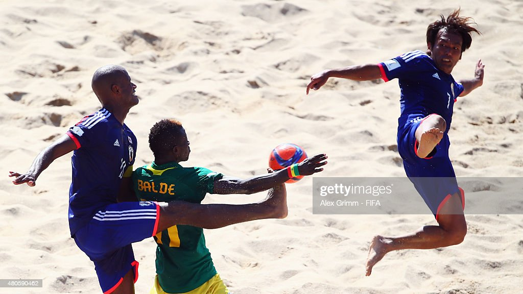 Ibrahima Balde (C) of Senegal is challenged by Ozu Moreira (L) and Teruki Tabata of Japan during the FIFA Beach Soccer World Cup Portugal 2015 Group A match beween Japan and Senegal at Espinho Stadium on July 13, 2015 in Espinho, Portugal.