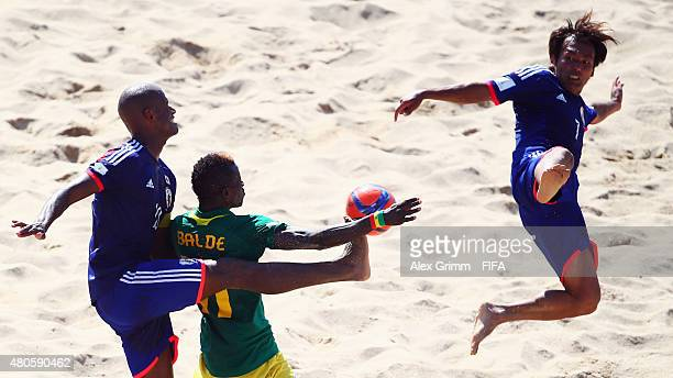 Ibrahima Balde of Senegal is challenged by Ozu Moreira and Teruki Tabata of Japan during the FIFA Beach Soccer World Cup Portugal 2015 Group A match...