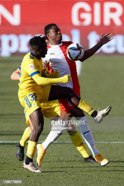 Ibrahima Kebe of Girona FC battles for the ball with Habeeb Omobolaji 'Boddy' Adekanye of Cadiz CF during the Copa del Rey round of 32 match between...