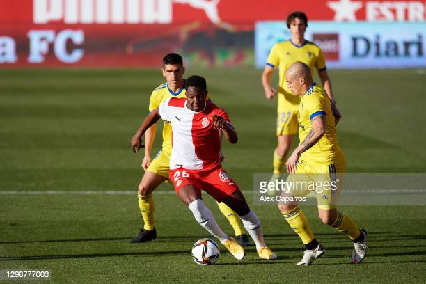 Ibrahima Kebe of Girona FC runs with the ball under pressure from Jorge Marcos Pombo and Jon Ander Garrido of Cadiz CF during the Copa del Rey round...