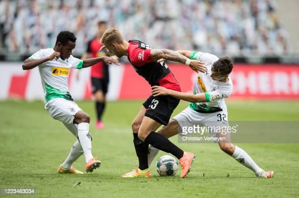 Ibrahima Traore Florian Neuhaus of Borussia Moenchengladbach and Arne Maier of Hertha BSC battle for the ball during the Bundesliga match between...