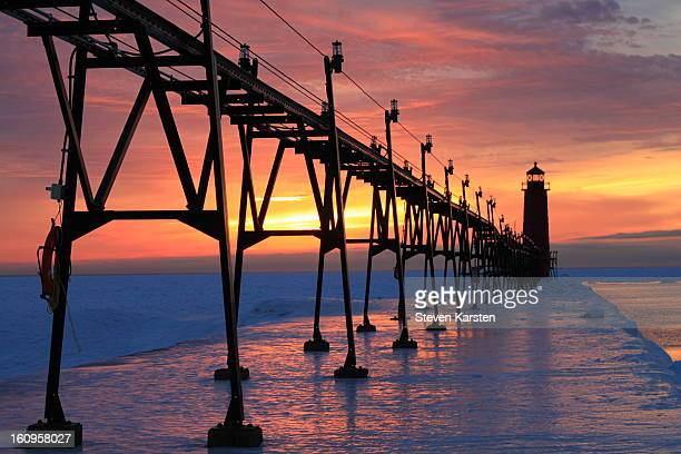 CONTENT] Ice and snow blanketing the pier catches light during a sunset in Grand Haven Michigan