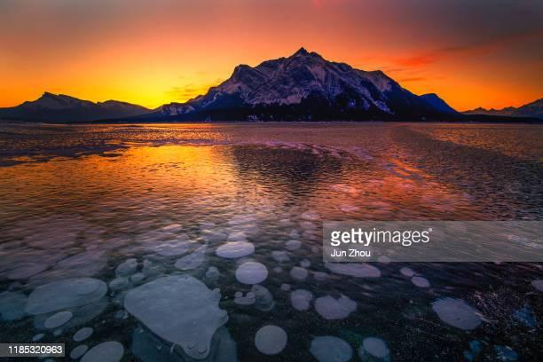 eisblase und sonnenaufgang bei banff - see abraham lake stock-fotos und bilder