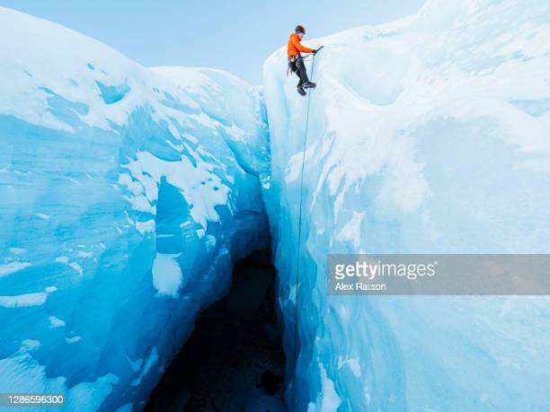 a ice climber at the lip of a tall ice face that drops steeply into a dark ice cave gets ready to be lowered back down. - bc stock pictures, royalty-free photos & images