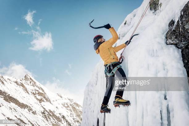 Escalador escalada cascada congelada en los Pirineos de hielo