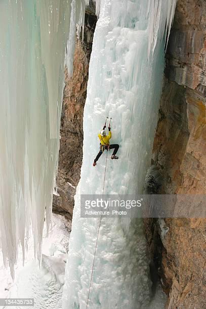 Ice Climber Extreme Adventurer on Steep Frozen Waterfall