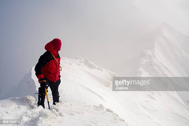 ice climber looking back along a mountain ridge - tottori prefecture stock photos and pictures