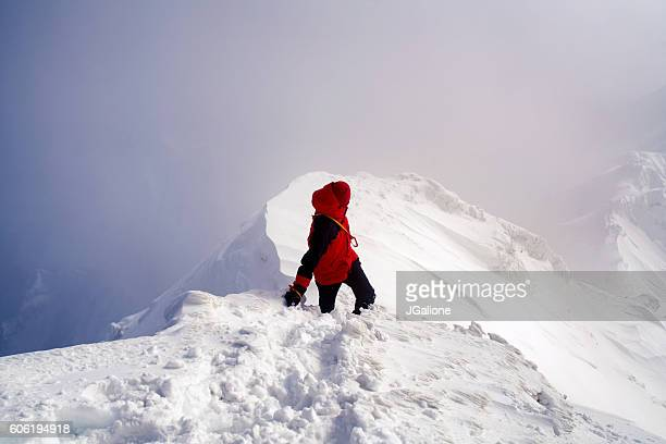 Ice climber looking back along a mountain ridge