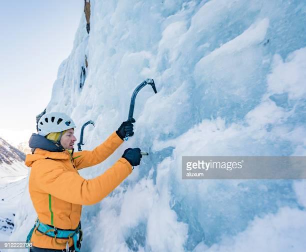 Ice climber placing ice screw
