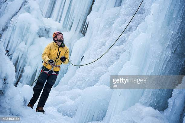 Ice Climber prepearing to climb on Frozen Waterfall