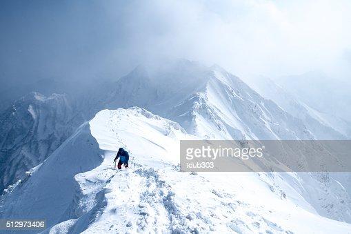 Ice Climber walks along mountain peak