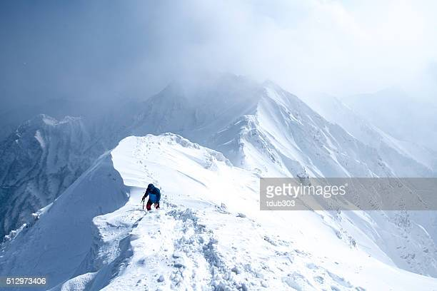 ice climber walks along mountain peak - snowcapped mountain stock pictures, royalty-free photos & images