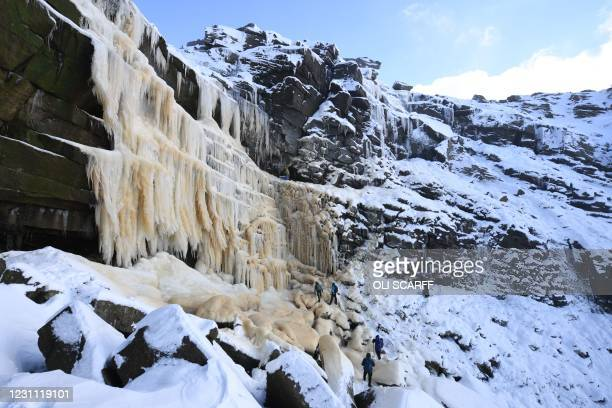 Ice climbers ascend Kinder Downfall, a frozen waterfall in the Peak District National Park, near Hayfield, northwest England as snow blankets the...