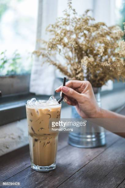 ice coffee in highball glass and woman hand holding straw on wood table