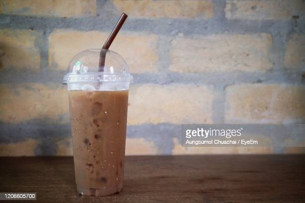 ice coffee on the wooden table with old brick wall, vintage style. food and drink concept. - coffee drink stock pictures, royalty-free photos & images