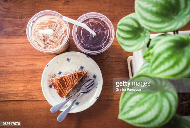 Ice coffee with cake and plant nature leaf on the wooden table in the coffee cafe.