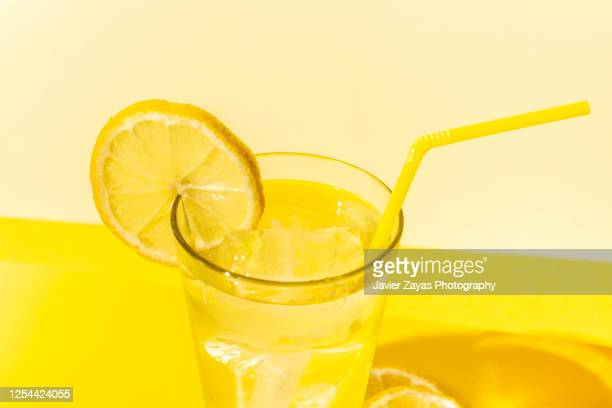 ice cold lemonade glass on yellow colored table - pops of bright color stock pictures, royalty-free photos & images