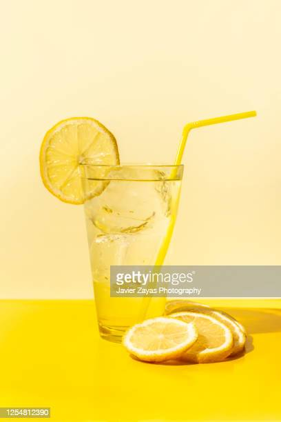 ice cold lemonade glass on yellow colored table - lemon soda stock pictures, royalty-free photos & images