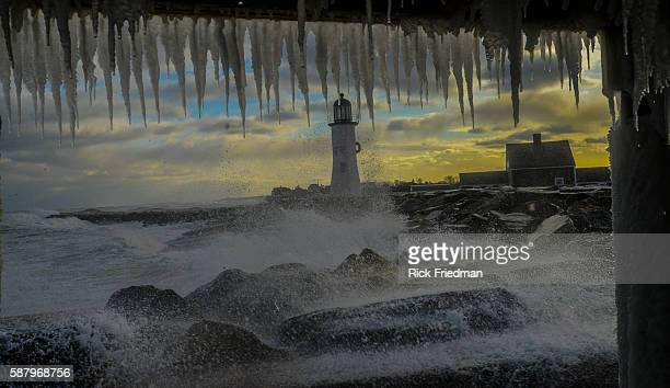 Ice covers a house near Scituate Lighthouse as waves wash over the seawall during a Nor'easter winter storm in Scituate MA 20 miles south of Boston...