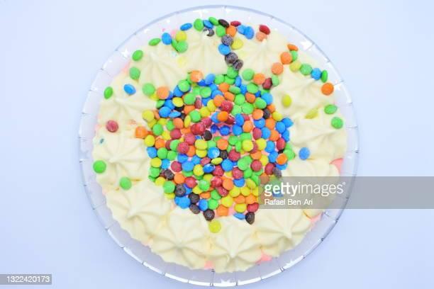 ice cream cake covered with colourful lollies isolated on white background - rafael ben ari stock-fotos und bilder