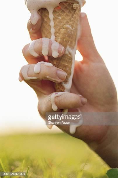 Ice cream cone melting on woman's hand, close-up
