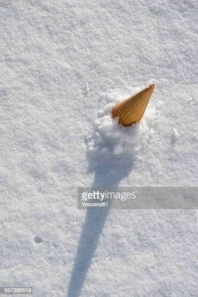 ice cream cone sticking in snow - irony stockfoto's en -beelden