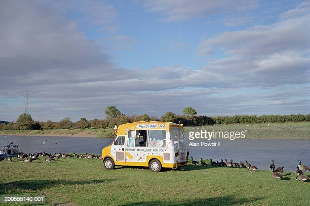 Ice cream van at riverbank surrounded by ducks
