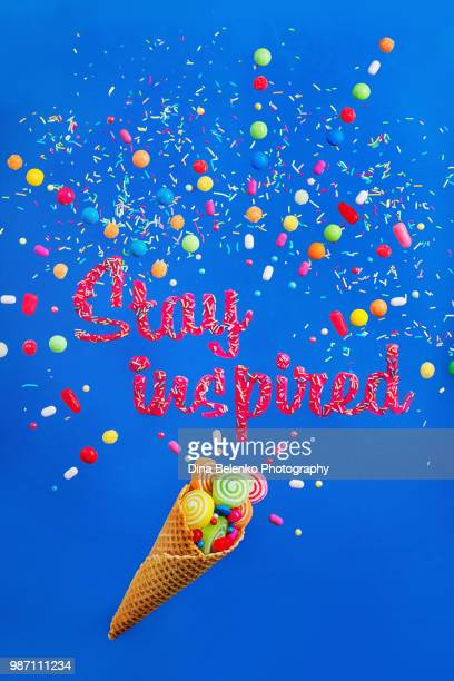 Ice cream waffle cone on a vibrant background with words Stay inspired made with glazing and sprinkles. Sweet motivation flat lay with candies and bonbons.