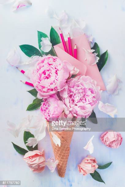 Ice cream waffle cone with peony flowers, letters, leaves, stationary and a pink envelope