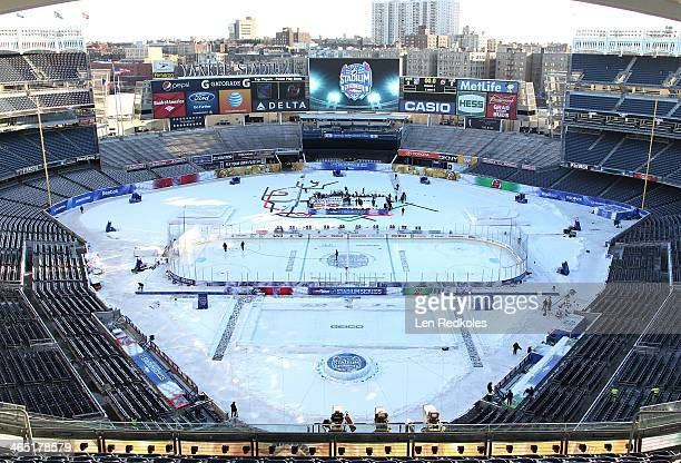 Ice crew workers spray the ice prior to the 2014 Coors Light NHL Stadium Series at Yankee Stadium on January 26, 2014 in New York City.