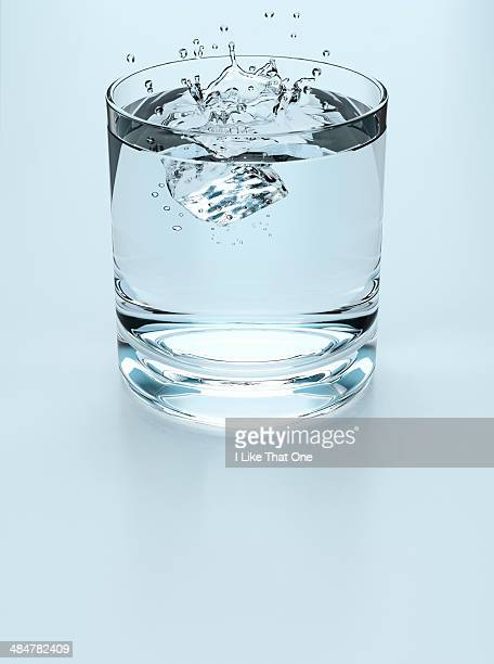 ice cube falling into a drinking glass of water - atomic imagery stock pictures, royalty-free photos & images