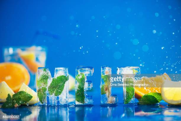 Ice cube lettering with frozen mint leaves, lemon slices and oranges on a blue background with water splashes. Text says Melt.
