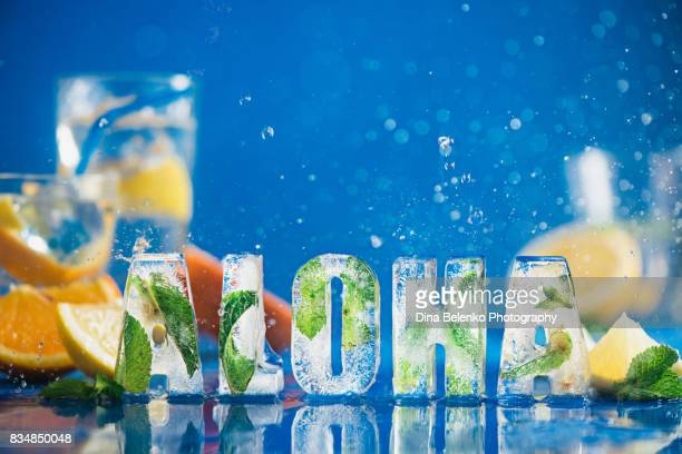 Ice cube lettering with frozen mint leaves, lemon slices and oranges on a blue background with water splashes. Text says Aloha.