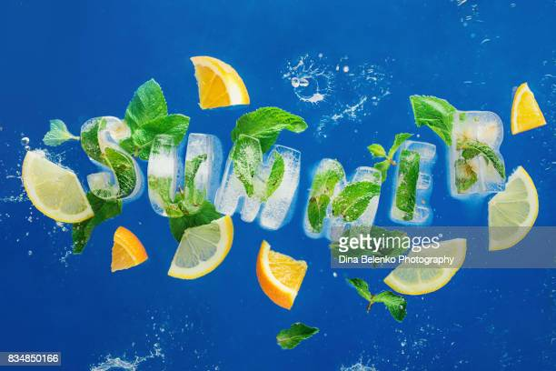 ice cube lettering with frozen mint leaves, lemon slices and oranges on a blue background with water splashes. text says summer - font imagens e fotografias de stock