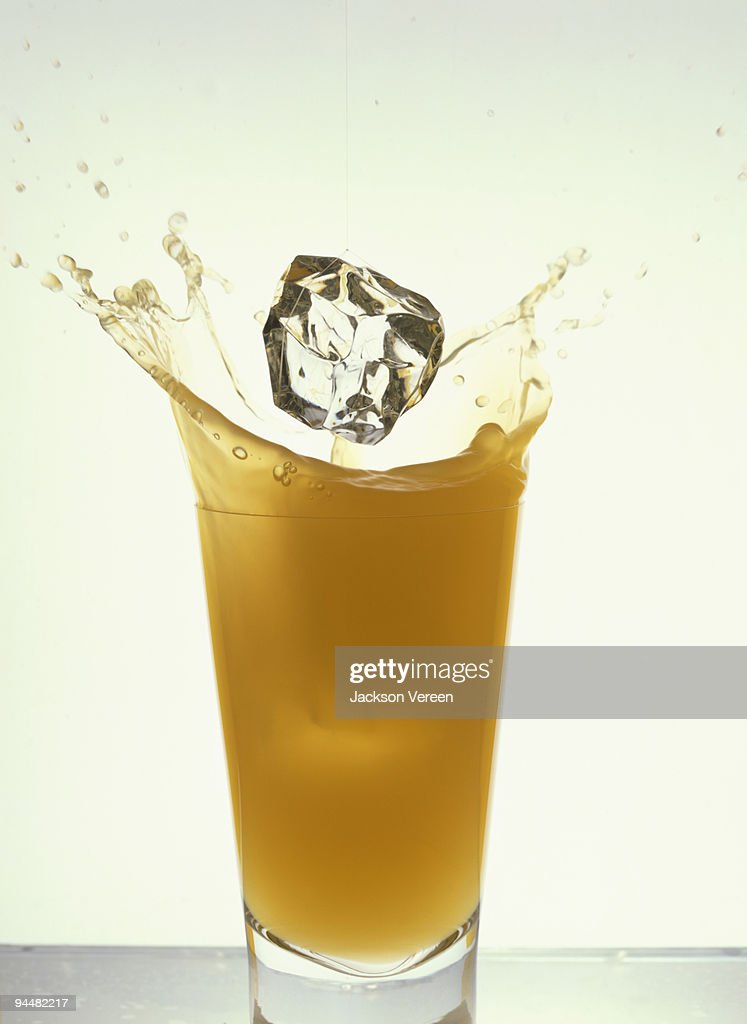 Ice cube splash in glass of orange juice : Stock Photo