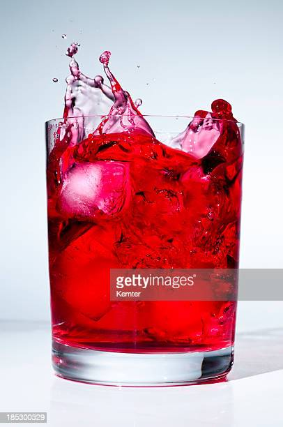 ice cube splashing into red liquid
