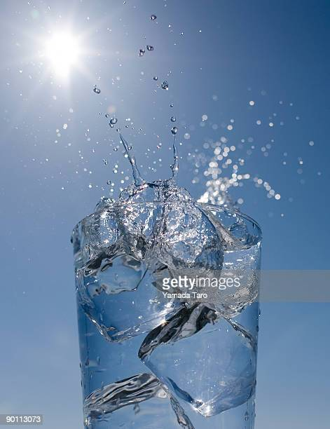 Ice cubes and splash water in glass on blue sky