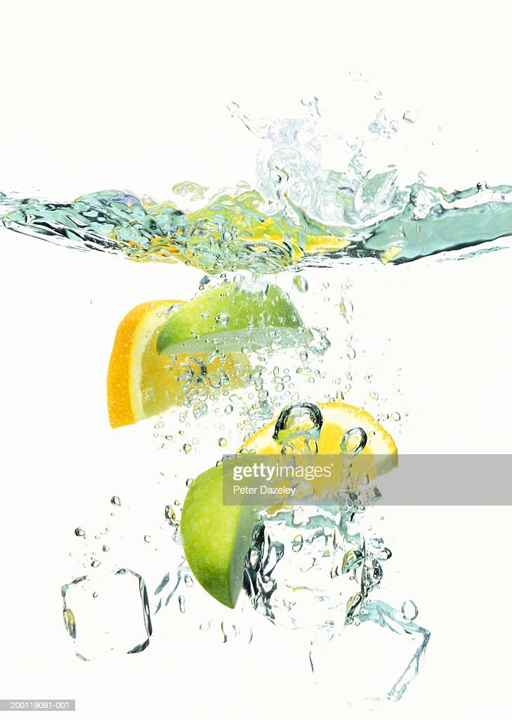 Ice cubes and wedges of  lemon and lime floating in liquid : Stock Photo