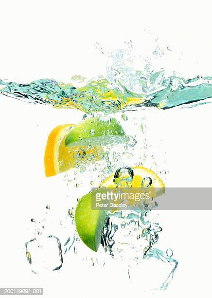 Ice cubes and wedges of  lemon and lime floating in liquid